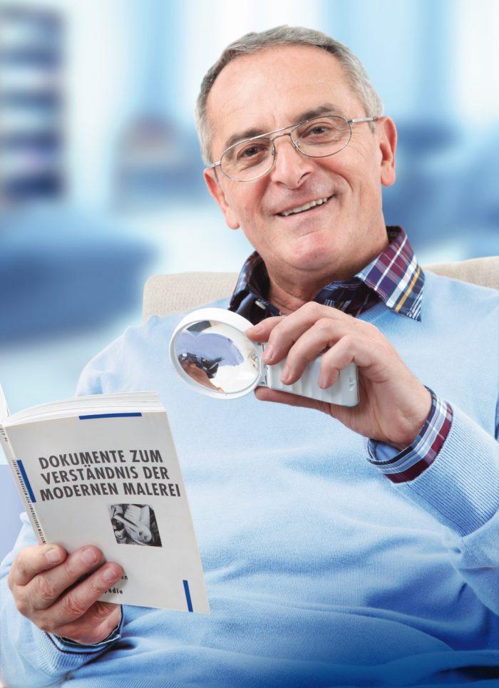 Herr mit Leuchtlupe in der Hand liest ein Buch