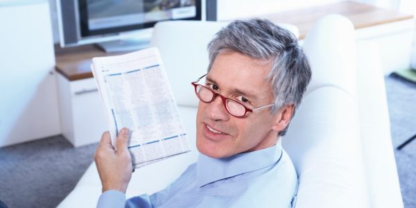 Herr trägt Lupenbrile beim Lesen