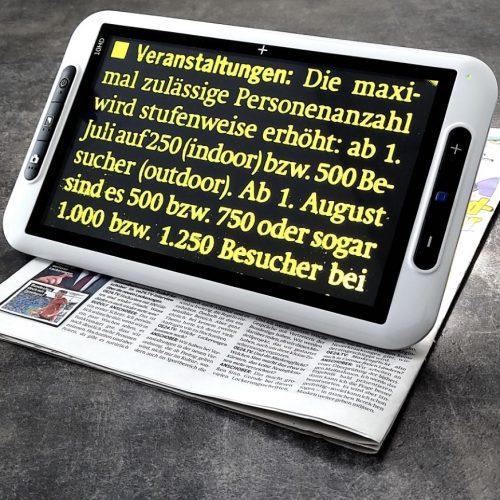 elektronische Lupe Pangoo 10 stehend auf Zeitung