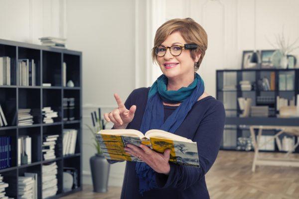 Frau mit OrCam und Buch