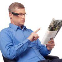 Mann mit einer OrCam liest Zeitung
